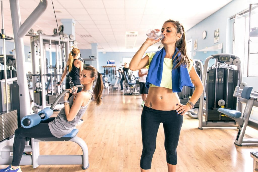 fitness model drinks water in a gym
