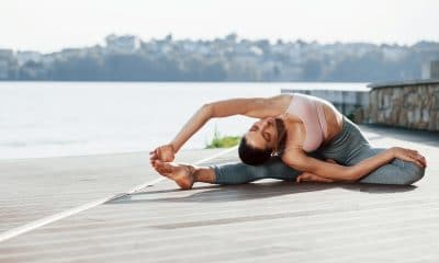 human body flexibility. young woman does exercises against lake