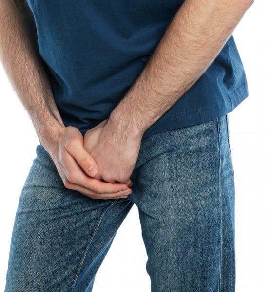 man holding his groin, isolated on white background. men's healt